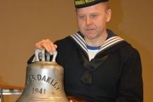 zdjęcie marynarza w stroju z okresu II wojny światowej z repliką dzwonu znalezionego we wraku ORP Kujawiak