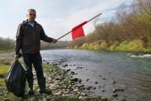fot. nadesłane przez Stowarzyszenie  Przyjaciele Raby, na zdjęciu mężczyzna na brzegu rzeki, trzymający w jednej ręce flagę Polski, w drugiej worek ze śmieciami