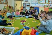 dzieci z muzycznymi bransoletami siedzące na dywanie
