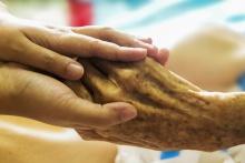 zdjęcie - dwie ręce osoby młodszej i starszej w opiekuńczym geście