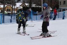 dwójka dzieci jeżdżąca na nartach