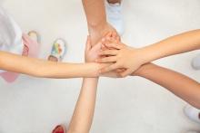 Zdjęcie przedstawia dłonie osób integrujących się, każda dłoń opiera się na poprzedniej..