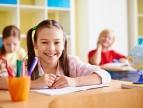 dziewczynka z uśmiechem siedząca w szkolnej ławce